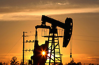 A China National Petroleum Corporation nodding donkey oil pump at sunset, Daqing, Heilongjiang province, China.