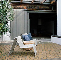 Two shaped metal chairs are set out on a paved terrace area. A sawn off tree trunk acts as a table between them