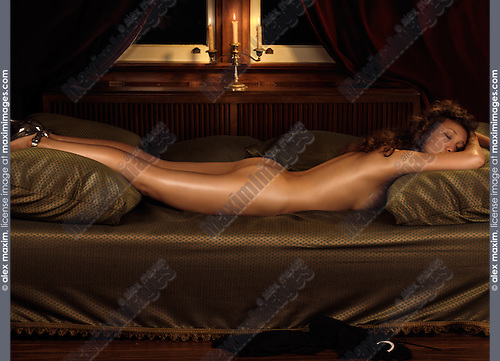 Beautiful young woman sleeping naked on a bed