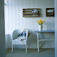 A Lloyd Loom chair and blue and white gingham covered table stand against a white painted tongue-and-groove clad wall