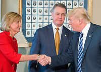 United States President Donald J. Trump, right, shakes hands with US Representative Claudia Tenney (Republican of New York), left, as US Senator David Perdue (Republican of Georgia), center, looks on prior to signing three Executive Orders concerning financial services at the Department of the Treasury in Washington, DC on April 21, 2017.<br /> Credit: Ron Sachs / Pool via CNP /MediaPunch