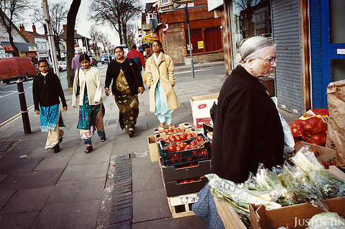 A group of Hindu women stroll down the street while a white British woman shops for groceries in Leicester city. ..Leicester has the biggest Gujarati population outside India and is expected to be the first city in the UK to have a majority non-white population within the next few years. It is one of the most ethnically-diverse cities in Europe. ....Picture taken April 2005 by Justin Jin