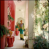 Fashion designer Liza Bruce wears a kaftan of her own design in the courtyard of her Moroccan home