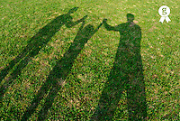 Shadow of people swinging a child, outdoors, elevated view (Licence this image exclusively with Getty: http://www.gettyimages.com/detail/200482615-001 )