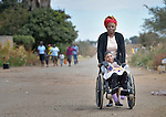 Tendai Nyamkondiwa pushes her niece, Ngonidzashe Rondozai, along a street in Harare, Zimbabwe.  Rondozai, 17, has cerebral palsy, and Nyamkondiwa, her aunt, is her primary caregiver. Rondozai uses an appropriately designed and fitted wheelchair provided by the Jairos Jiri Association with support from CBM-US.
