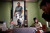 A Tamil-Tiger (LTTE) official in Kilinochchi town discusses tsunami relief in the northeastern coast of Sri Lanka, an area ravaged also by civil war. Behind him stands a poster of the reclusive Tiger leader Velupillai Prabhakaran. .The December 26, 2004 tsunami killed around 40,000 people along Sri Lanka's southern, eastern and northern shores, tearing thousands of families apart. .The bulk of the dead were women and children - husbands lost young brides and around 4,000 children lost one or both parents. .Even before the tsunami struck, people here in the northeast had already been displaced four times by the Tigers' two-decade war for autonomy. .In some places, the scars of war and the tsunami have become one. Remnants of walls torn down by waves are pockmarked with bullet holes and shrapnel from shells fired before a 2002 ceasefire plunged a civil war that killed over 64,000 people into limbo. ...Picture taken March 2005 by Justin Jin.