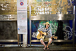 Musician You Waki busks under the railway tracks at  Shimokitazawa, Setagaya Ward, Tokyo, Japan..Photographer: Robert Gilhooly