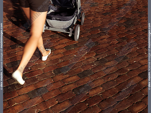 Woman walking with a stroller on brick cobbled street, closeup of legs with dynamic motion blur