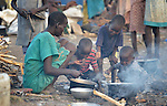 A mother and her children, newly displaced by war, cook food inside a United Nations base in Malakal, South Sudan. More than 20,000 civilians have lived inside the base since shortly after the country's civil war broke out in December, 2013, but renewed fighting in 2015 drove another 5,000 people, including these people, into the relative safety of the camp.
