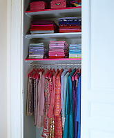 This small wardrobe is filled with neat piles of colourful clothes and a row of items on hangers