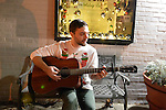 BRANDON PETERSON, a guitarist in the band Cloud Caverns, plays guitar outdoors at the Jingle Boom Holiday Bash, at the Main Street Gallery of Huntington Arts Council. He's wearing a funny Christmas sweater with cats in Christmas stockings, and prizes were awarded to people wearing the most creative or Ugly Sweaters. Sparkboom, an HAC project, provides events such as this geared to Gen-Y, 18-34 years of age, to address the 'brain drain' of creative young professionals of Long Island.