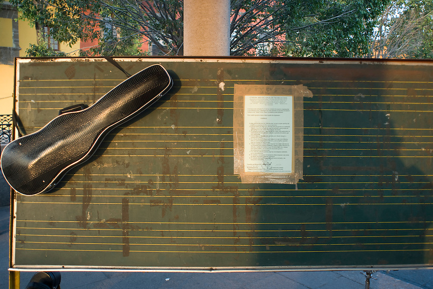 A violin case rests next to a document which contains the membership rules of the Mariach syndicate in Plaza Garibaldi where Mariachis gather to be hired in Mexico City, Friday, Jan. 4, 2008