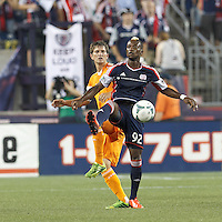 New England Revolution substitute forward Dimitry Imbongo (92) collects a high pass as Houston Dynamo defender Bobby Boswell (32) pressures.  In a Major League Soccer (MLS) match, Houston Dynamo (orange) defeated the New England Revolution (blue), 2-1, at Gillette Stadium on July 13, 2013.