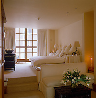 In this spacious all-white bedroom the sleeping area is raised above the sitting area