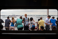 Comuters and tourists enjoy the views from the Staten Island Ferry. Summer in New York City, New York, USA