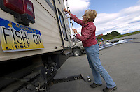 Ann Korn, of Wisconsin, unlocks her camper in a parking lot on the Cook Inlet beach at the mouth of the Kenai River in Kenai, Alaska. She and her husband Cliff (not pictured) were on the beach to watch her son dipnet salmon.