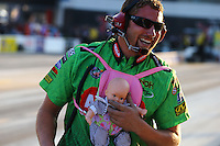 Sep 13, 2013; Charlotte, NC, USA; A crew member for NHRA top fuel dragster driver Terry McMillen wears a baby doll around his body during qualifying for the Carolina Nationals at zMax Dragway. The doll was a tribute to driver McMillen who became a father earlier this week. Mandatory Credit: Mark J. Rebilas-