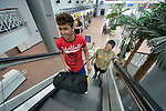 Edwin Chacon, an asylum seeker from Honduras, rides an escalator in the Valley International Airport in Harlingen, Texas, accompanied by Cindy Johnson, a United Methodist deaconess. Johnson helps transport immigrants on behalf of the Posada Providencia in San Benito, where Chacon, 18, stayed for several days after being released by immigration authorities pending a judicial hearing on his asylum request. He was on his way to stay with a relative elsewhere in the United States.<br /> <br /> Sponsored by the Catholic Sisters of Divine Providence, the Posada Providencia provides a safe place for people in crisis from all over the world who are seeking legal refuge in the United States.