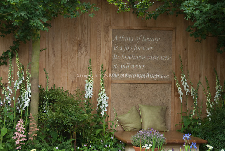 Keats A thing of beauty is a joy forever motto on garden fence wall, with bench, cushions, place to relax, foxglove white flowers, tree, privacy in backyard