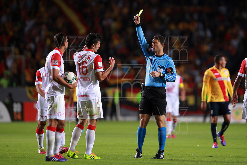 MORELIA - MEXICO -28 -01-2014: Juan Soto (Der.), arbitro, muestra tarjeta amarilla a Daniel Torres (Cent.) jugador  del Independiente Santa Fe de Colombia durante partido por la primera fase, llave G5 de la Copa Libertadores en el estadio Morelos de la ciudad de Morelia. / Juan Soto (R), referee of show yellow card to Daniel Torres (C) player del Independiente Santa Fe of Colombia during a match for the first fase, g5 key in Morelos stadium in Morelia city, Photo: VizzorImage  / Manuel Velasquez / Jam Media / Cont