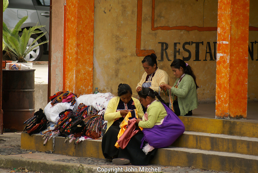 Mexican indigenous women sitting on a step doing embroidery in the village of La Antigua, Veracruz, Mexico.