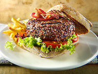 Peppered beef burger with bacon in a wholemeal bun with chips photos. Funky Stock Photos