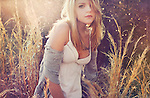 Close up of young woman with blonde hair outdoors in garden with long grass