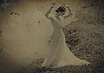 atmospheric and ghostly image of a young woman with closed eyes standing with raised hands wearing long flowing white dress
