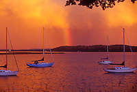 A rainbow is seen behind sailboats anchored in the lower harbor of Marquette, Mich.