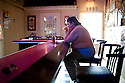 A woman drinks alone in a bar at noon. <br />