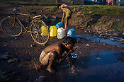 A cyclist fills up drinking water in Bokapahari village in Jharia, outside of Dhanbad in Jharkhand, India.   Photo: Sanjit Das/Panos