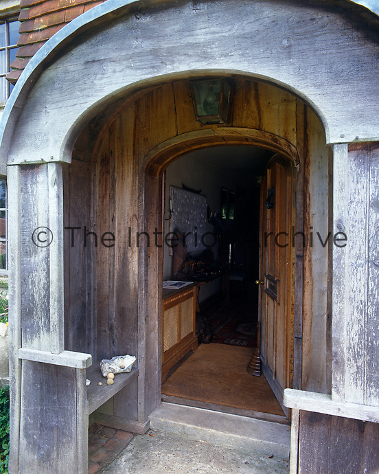 An open front door leads from a faded wooden porch into the entrance hall