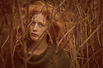 Female youth with curly red hair and piercing green eyes standing outdoorssurrounded by branches.
