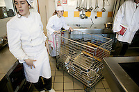 A student wheels in a cart of clean bowls and containers during a class at the Ecole Superieure de Cuisine Francaise Gregoire Ferrandi cooking school in Paris, France, 18 December 2007.