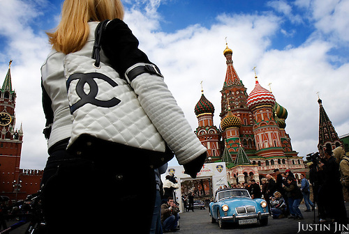 A woman with a Chanel bag looks at an Old-Timer car show in front of Moscow's St. Basils Cathedral on the Red Square.