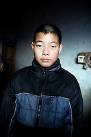 Fan Wen Jie, 11, was orphaned in 2006 and now lives with his grandparents on a half hectare of land in rural Fanzhuan Village, Jiangsu Province, China.  The boy's father died in a car crash in 2005, and his mother remarried in 2006, abandoning the boy, though she still periodically sends money to help the family.  The boy's grandparents are frequently ill, and the meager income from farming cannot support his schooling.   ..At the time of the picture, China's Amity Foundation charity, was investigating the family's situation in preparation to raise money to financially support these children and other orphans in similar situations.  With Amity's support, each orphan, aged 6-12, would receive approximately 1,400 RMB annually (about 200 USD) to pay for the cost of living. Amity works to keep children out of the institutional orphanages in China, preferring to provide monetary assistance that can help maintain a family environment for the orphans it helps..