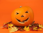 Carved smiling pumpkin on colorful fall leaves. Jack-o'-lantern Halloween symbol. Isolated on orange background.