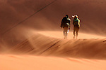 Africa, Namibia, Sossusvlei. Two people walking the windblown dunes at Sossussvlei,