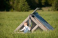 A male toddler in bibs peeks into a chicken coop while playing on a farm.