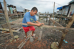 """A man works constructing a new house amid the rubble of his old dwelling in Tacloban, a city in the Philippines province of Leyte that was hit hard by Typhoon Haiyan in November 2013. The storm was known locally as Yolanda. The man's house lies within a controversial 40 meter """"no build"""" zone that prohibits such construction. The ACT Alliance has been active here and in affected communities throughout the region helping survivors to rebuild their homes and recover their livelihoods."""