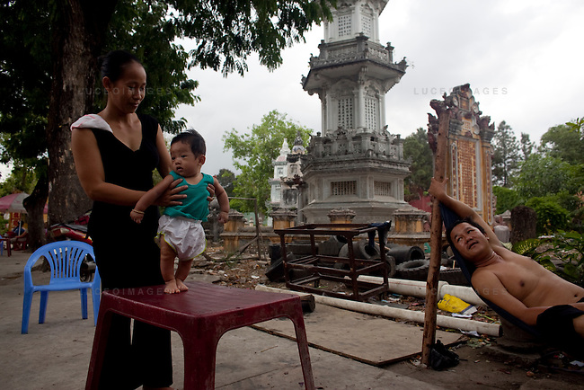 A family relaxes in front of the cemetery for Buddhist monks at the Giac Vien Pagoda in District 11 in Ho Chi Minh City, Vietnam. Photo taken Monday, May 3, 2010...Kevin German / LUCEO