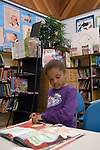 Oakland CA 2nd grade student looking over book to borrow in school library