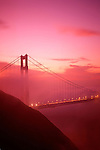 Golden Gate Bridge enveloped in thick fog at sunrise from Marin Hills above Bay, San Francisco, California USA  The Golden Gate connects San Francisco penninsula and Marin penninsula and is nearly two miles long,  San Francisco, California USA.