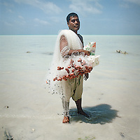 A young man carries a net to catch reef fish in the lagoon and a bag in which to carry them.