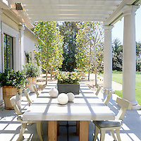 A table topped with a concrete slab in the outdoor dining room is framed by palladian columns