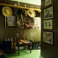 A collection of hats and bags hangs from a wall of hooks in this boot room which is decorated with framed prints