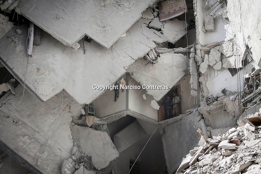Syrian residents stand at one destroyed building as they look for bodies after an aistrike hits a residential area in Al-Ansari, a neighborhood under control of the rebel fighters in Aleppo, Syria.