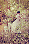 atmospheric and ghostly photo of beautiful young caucasian woman walking outdoors in sunny day in woodland wearing long flowing white dress