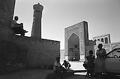 Carpet, and souvenir, sellers sit in the shade of the 16th century Kalan Mosque , minaret and Medressa, in Bukhara, the once hugely important Islamic city on the old Silk Road trading route. Uzbekistan.