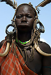 Woman with clay lip plate and face painted, wearing headgear, Mursi Tribe, Mago National Park, Lower Omo Valley, Ethiopia, portrait, person, one, tribes, tribal, indigenous, peoples, Southern, ethnic, rural, local, traditional, culture, primitive.Africa....